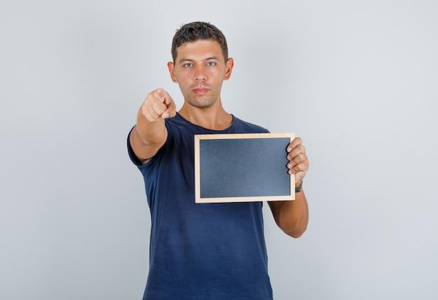 Młody mężczyzna wskazując palcem na aparat z tablicą w granatowej koszulce, widok z przodu.