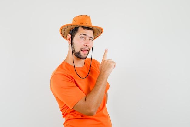 Młody mężczyzna, wskazując w górę, mrugając okiem w pomarańczowym t-shirt, kapelusz, widok z przodu.