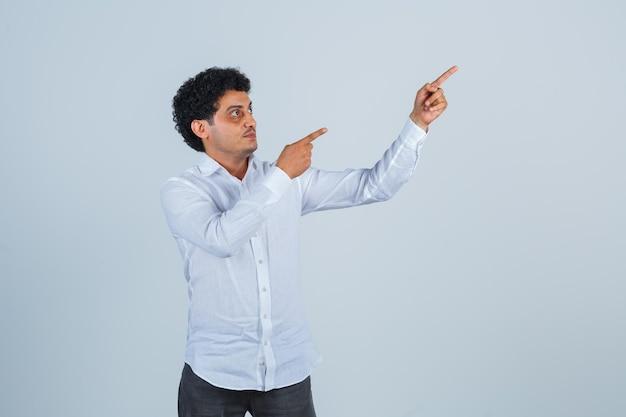 Młody mężczyzna, wskazując w górę w białej koszuli, spodniach i patrząc skupiony, widok z przodu.