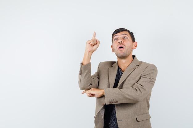 Młody mężczyzna, wskazując w górę w szarawo brązową kurtkę i patrząc skupiony. przedni widok. miejsce na tekst