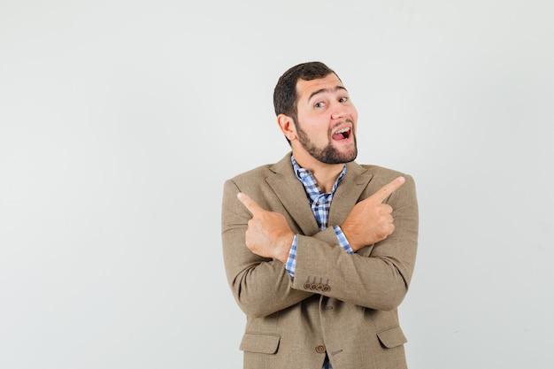 Młody mężczyzna wskazując w koszulę, kurtkę i wesoły wyglądający.