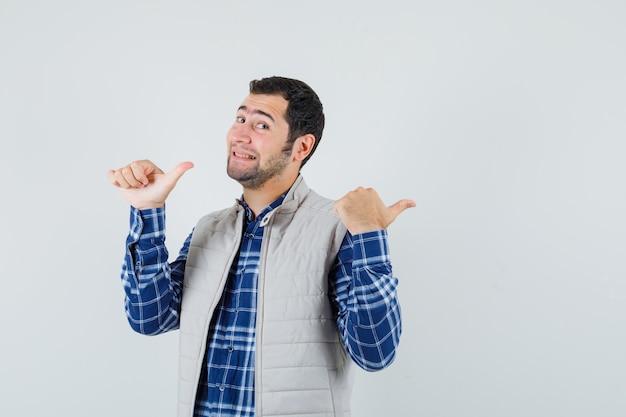 Młody mężczyzna, wskazując w koszuli, kurtka bez rękawów, widok z przodu.