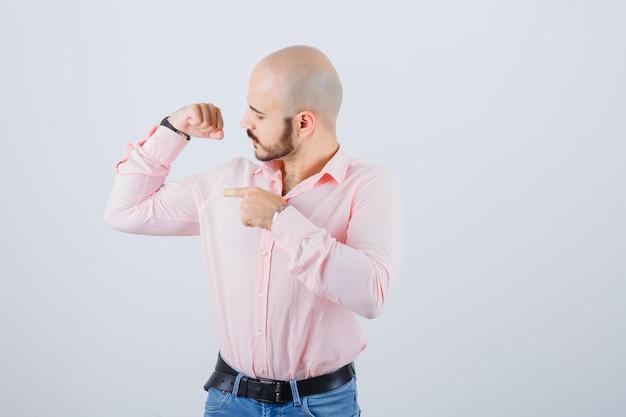 Młody mężczyzna wskazujące mięśnie ramion w koszuli, dżinsach i patrząc dumny, widok z przodu.