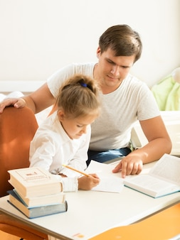 Młody mężczyzna wskazujący na błąd w notatniku córki
