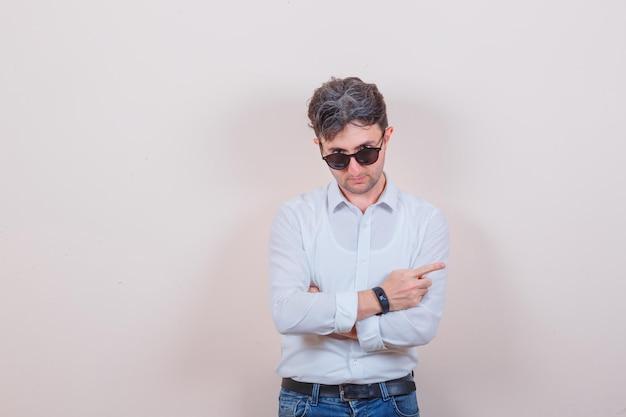 Młody mężczyzna wskazujący na bok, patrzący przez okulary w białej koszuli, dżinsach