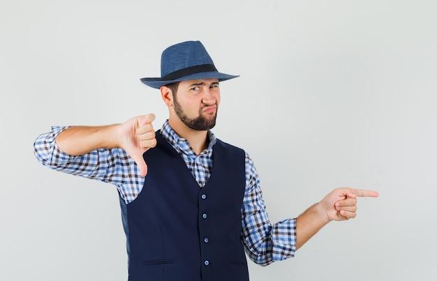 Młody mężczyzna wskazujący na bok, pokazujący kciuk w dół w koszuli, kamizelce, kapeluszu i wyglądający na niezadowolonego.