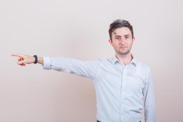 Młody mężczyzna wskazujący na bok w białej koszuli i wyglądający pewnie