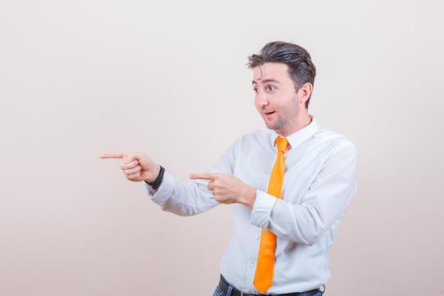 Młody mężczyzna wskazujący na bok w białej koszuli, krawacie i patrzący na zdziwionego