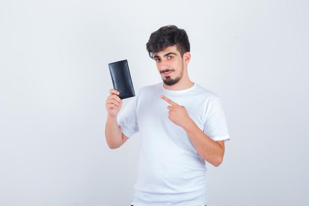 Młody mężczyzna wskazujący na portfel w białej koszulce i wyglądający na pewny siebie