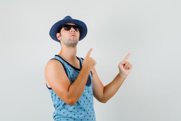Młody mężczyzna wskazujący na prawy górny róg w niebieskim podkoszulku, kapeluszu i patrząc skupiony. przedni widok.