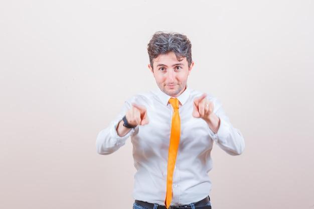 Młody mężczyzna wskazujący na przód w koszuli, dżinsach i wyglądający jowialnie