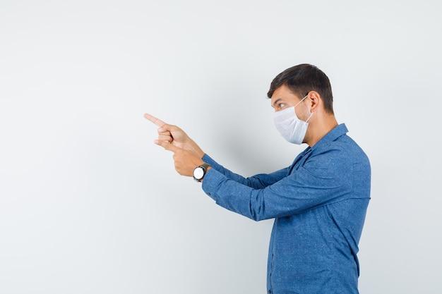 Młody mężczyzna wskazujący na siebie w niebieskiej koszuli, masce i patrzący na siebie. .