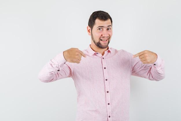 Młody mężczyzna wskazujący na siebie w różowej koszuli i wyglądający dumnie