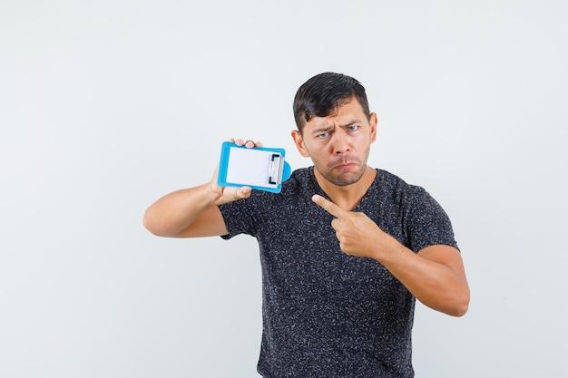 Młody mężczyzna wskazujący na swój malutki notatnik w czarnej koszulce i wyglądający na obrażonego. przedni widok.
