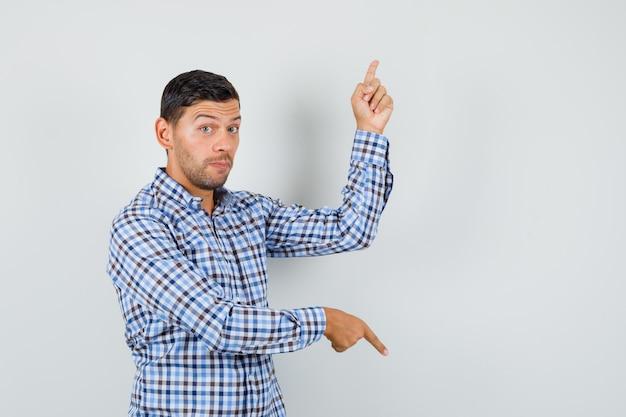Młody mężczyzna wskazujący palcami w górę iw dół w kraciastej koszuli i wyglądający na niezdecydowanego