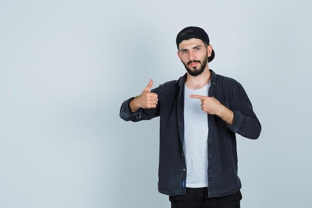Młody mężczyzna wskazujący palcem i pokazujący kciuk w górę