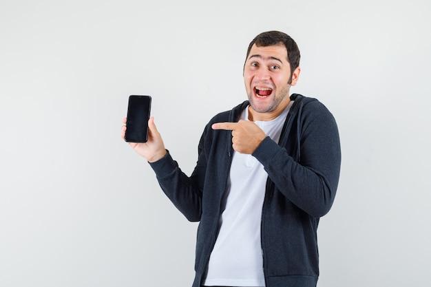 Młody mężczyzna wskazujący smartfon, uśmiechnięty w białej koszulce i czarnej bluzie z zamkiem błyskawicznym i wyglądający na szczęśliwego. przedni widok.