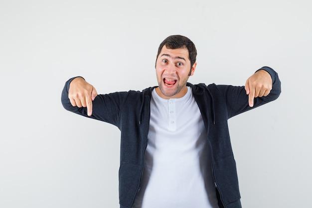 Młody mężczyzna wskazujący w dół z palcami wskazującymi w białej koszulce i czarnej bluzie z kapturem zapinanej na suwak i wygląda optymistycznie. przedni widok.