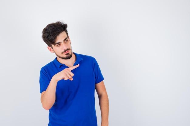 Młody mężczyzna wskazujący w prawo palcem wskazującym w niebieskiej koszulce i wyglądający poważnie
