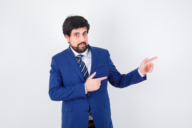 Młody mężczyzna wskazuje na bok w koszuli, kurtce, krawacie i patrząc pozytywnie, widok z przodu.