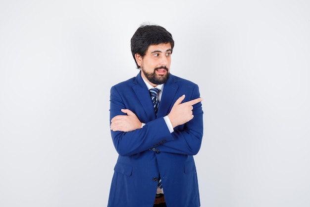 Młody mężczyzna wskazuje na bok w koszuli, kurtce, krawacie i patrząc radośnie. przedni widok.