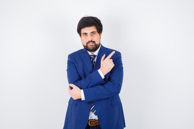 Młody mężczyzna wskazuje na bok w koszuli, kurtce, krawacie, widok z przodu.