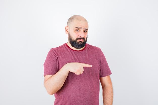Młody mężczyzna wskazuje na bok w różowej koszulce i wygląda na przestraszonego. przedni widok.