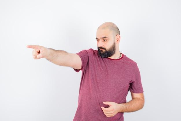 Młody mężczyzna wskazuje na bok w t-shirt i wygląda pewnie. przedni widok.