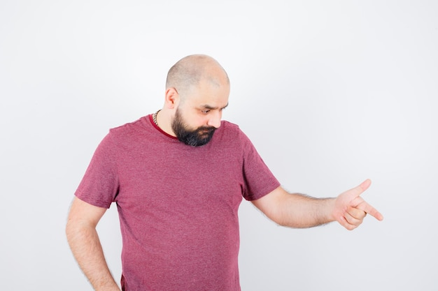 Młody mężczyzna wskazuje w dół i patrzejący rozważny, przedni widok w t-shirt.