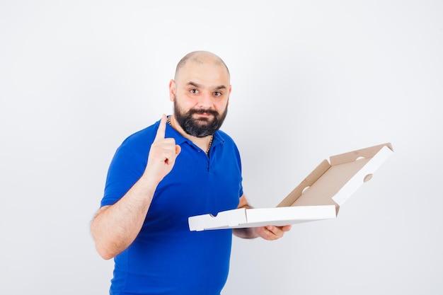 Młody mężczyzna wskazuje w górę w t-shirt i wygląda na szczęśliwego. przedni widok.