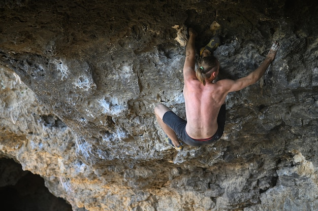 Młody mężczyzna wspinacz bouldering ściany skalnej w jaskini