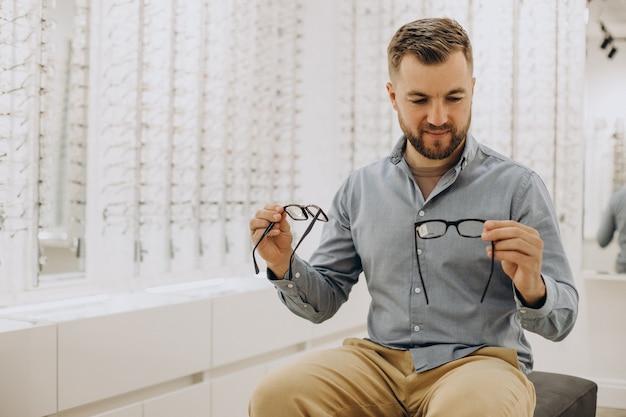 Młody mężczyzna wybiera okulary w sklepie optycznym