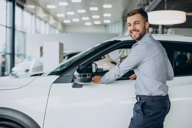 Młody mężczyzna wybierający samochód w salonie samochodowym