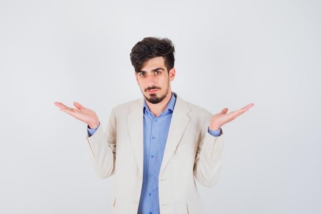 Młody mężczyzna wyciąga ręce w pytający sposób w niebieskiej koszulce i białej marynarce i wygląda poważnie
