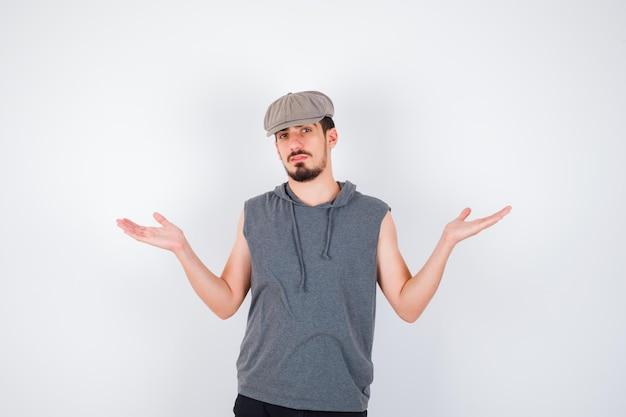 Młody mężczyzna wyciąga ręce w pytający sposób w szarej koszulce i czapce i wygląda na zakłopotanego