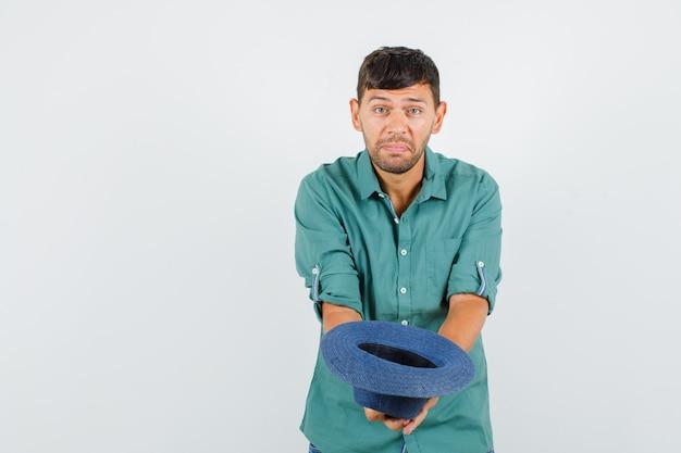 Młody mężczyzna wyciągający kapelusz w koszuli i wyglądający biednie.