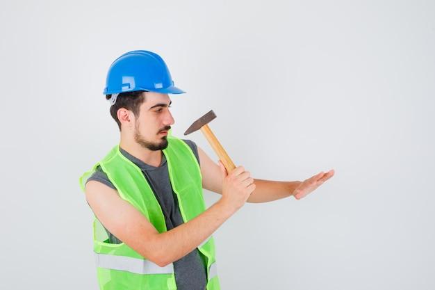 Młody mężczyzna wyciągający topór w kierunku dłoni w mundurze budowlanym i wyglądający na skupionego