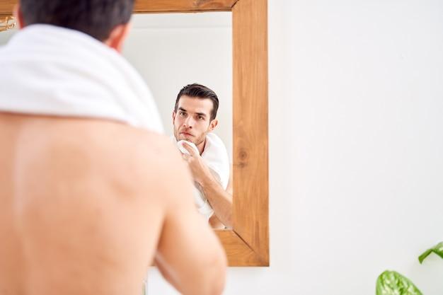 Młody mężczyzna wyciera ręcznik stojąc przy lustrze w wannie rano