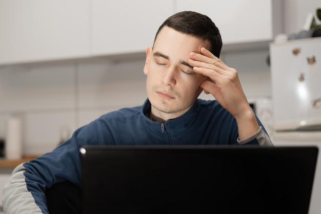 Młody mężczyzna wygląda zestresowany podczas korzystania z laptopa do pracy w domu