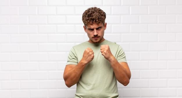 Młody mężczyzna wyglądający na pewnego siebie, zły, silny i agresywny, z pięściami gotowymi do walki w pozycji bokserskiej