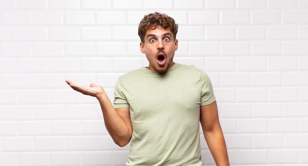 Młody mężczyzna wyglądający na zaskoczonego i zszokowanego, z opuszczoną szczęką, trzymający przedmiot z otwartą dłonią z boku