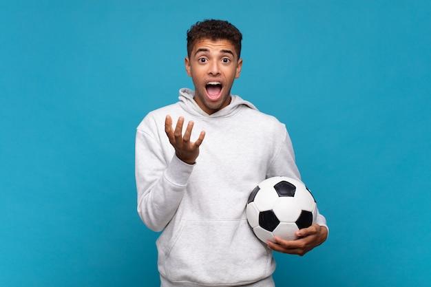 Młody mężczyzna wyglądający na zdesperowanego i sfrustrowanego, zestresowanego, nieszczęśliwego i zirytowanego, krzyczącego i wrzeszczącego. koncepcja piłki nożnej