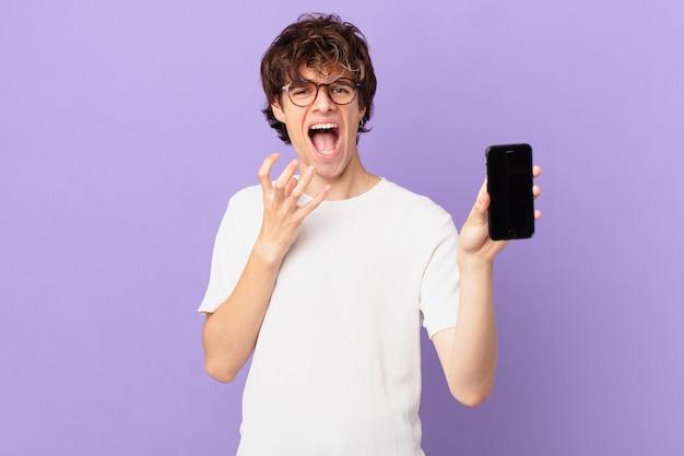 Młody mężczyzna wyglądający na zdesperowanego, sfrustrowanego i zestresowanego, trzymający komórkę