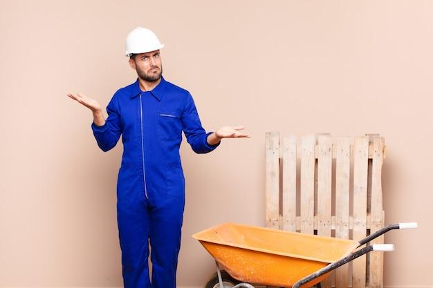 Młody mężczyzna wyglądający na zdziwionego, zdezorientowanego i zestresowanego, zastanawiający się między różnymi opcjami, czujący niepewną koncepcję budowy