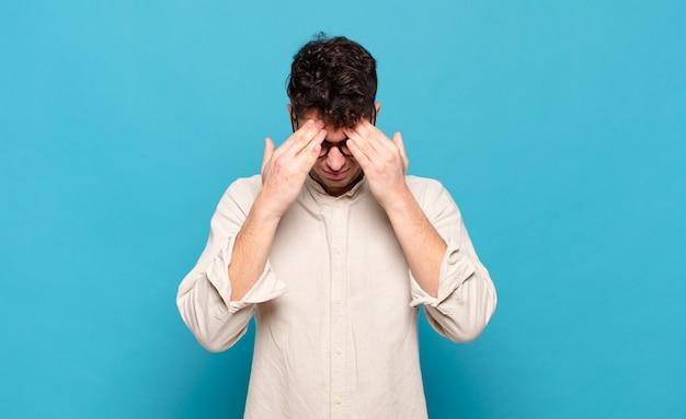 Młody mężczyzna wyglądający na zestresowanego i sfrustrowanego, pracujący pod presją, bóle głowy i kłopoty