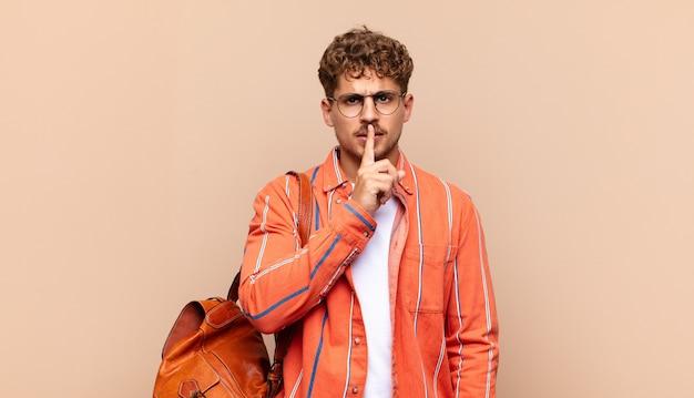 Młody mężczyzna wyglądający poważnie i krzywo, z palcem przyciśniętym do ust, domagający się ciszy lub spokoju, dochowania tajemnicy. koncepcja studenta