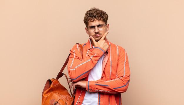 Młody mężczyzna wyglądający poważnie, zamyślony i nieufny, z jedną ręką skrzyżowaną i ręką na brodzie, opcje ważenia
