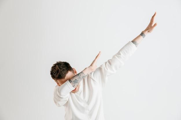 Młody mężczyzna wykonuje dab ruch rękami na szarej ścianie.