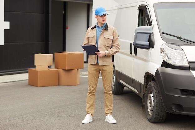Młody mężczyzna wypełniając dokument i wysyłając ładunek, ładuje pudła do furgonetki