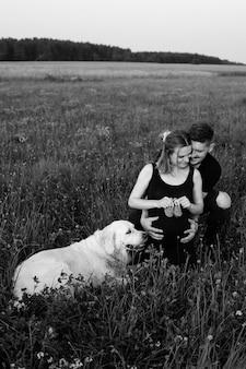Młody mężczyzna wyraża czułość i troskę swojej ciężarnej żonie, która trzyma w rękach dziecięce buciki, obok niej leży ich najmądrzejszy pies. czarno-białe zdjęcie. śmieszne chwile. nowe życie.